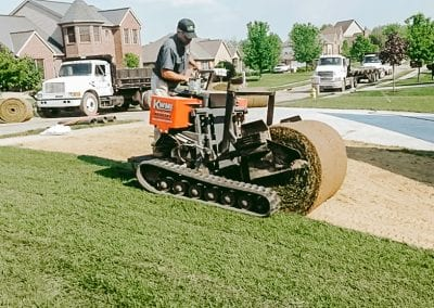 employee laying sod in residential neighborhood